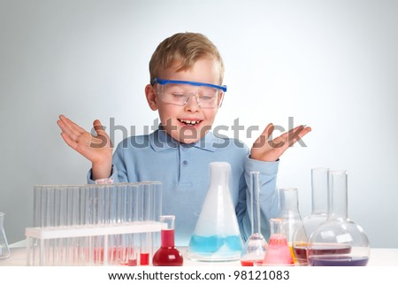 A little boy looking flask during chemical experiment - stock photo