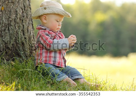a little boy playing in a cowboy hat on nature - stock photo