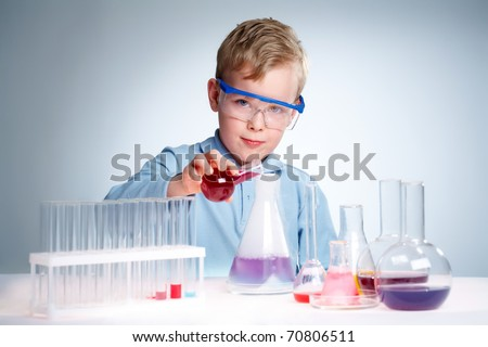 A little boy pouring liquid into a flask and looking at camera - stock photo