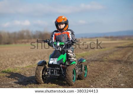 A little boy rides his electric ATV quad. - stock photo