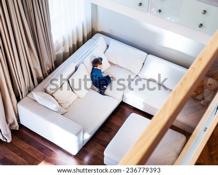 A little boy siting in big modern living room , top view. - stock photo