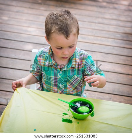 A little boy sitting at a crafts table having fun painting and decorating Easter eggs.  He colors an egg in a bowl with green dye while outdoors in the spring season.  Part of a series. - stock photo