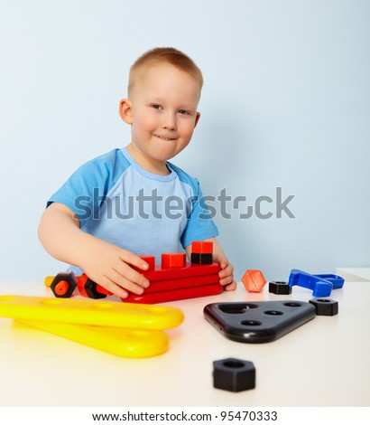 A little boy sitting at a table. Playing - stock photo