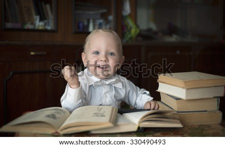 A little boy sitting at a table with books - stock photo