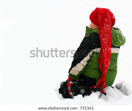a little boy sitting in the snow - stock photo