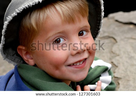 A little boy taking a break and resting on a rock by a creek - stock photo