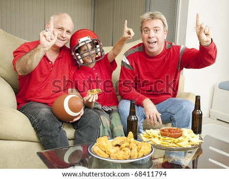 A little boy watching the super bowl with his father and uncle. - stock photo