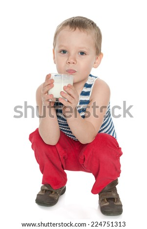 A little boy with a glass of milk on the white background - stock photo