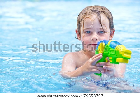 A little boy with a water gun in the pool. - stock photo