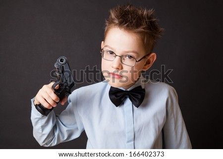 A little boy with a weapon on a black background - stock photo