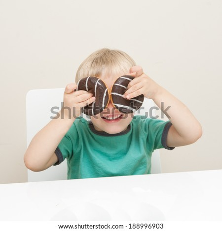 A little boy with donuts over his eyes.  Could symbolise unhealthy eating in children or appeal to those considering buying donuts - stock photo