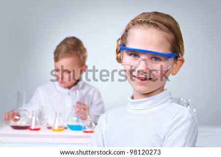 A little boy working with liquid with his assistant looking at camera at foreground - stock photo