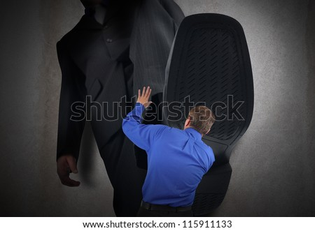 A little business man is under a big bosses foot about to crush or step on him. His hands are in the air scared. - stock photo