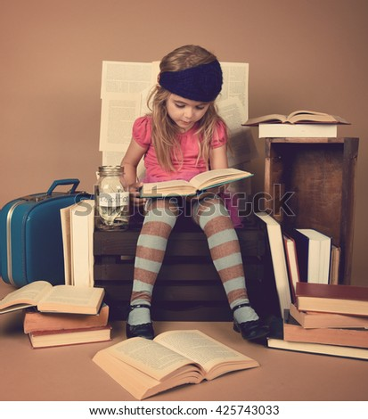A little child girl is reading library books with a jar of money for education. Use it for a school, tuition or college concept. - stock photo