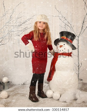A little child is building a snowman in a studio scene with white trees and fake snow on the ground for a season or Christmas concept - stock photo