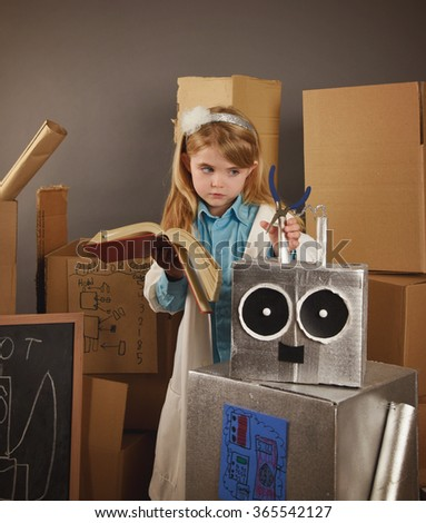 A little child is building an repairing a robot toy made out of cardboard for a career or education concept about engineering or math. - stock photo