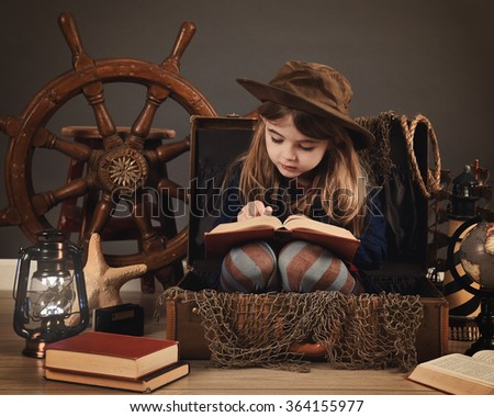 A little child is reading an old book sitting in a travel suitcase with sea props for an imagination or education concept. - stock photo