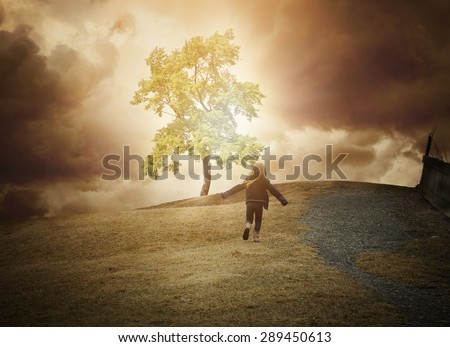 A little child is running up a hill to a glowing tree of light with dark clouds in the background. Use it for a hope, freedom or happiness concept. - stock photo