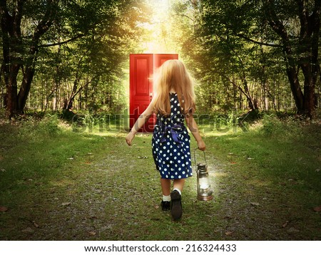 A little child is walking in the woods holding a light and looking at a glowing red door on the path for a mystery or imagination concept. - stock photo