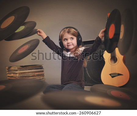 A little child is wearing music headphones with retro vinyl records spinning around on a gray background with an amp and guitar for a party or entertainment concept. - stock photo