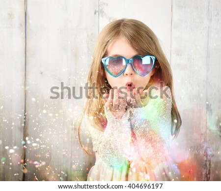 A little child is wearing sunglasses and blowing magical rainbow glitter sparkles in the air for a celebration, happiness or party idea. - stock photo