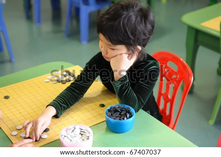 A little chinese kid learning to play go(weiqi) game - stock photo