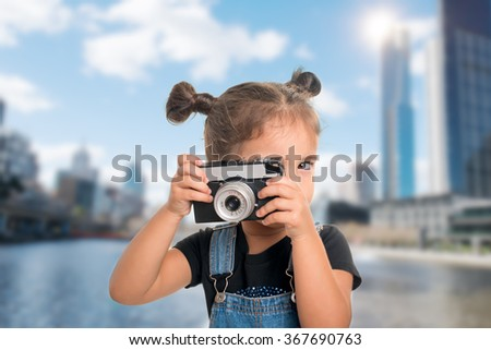 A little cute  baby girl taking a picture  with vintage camera over city background - stock photo