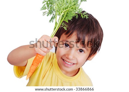 A little cute child holding a fresh carrot in hand - stock photo