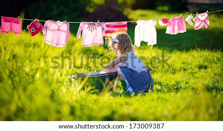 A little cute girl doing the laundry in a small aluminium basin near the clothesline in the meadow on a sunny summer day - stock photo