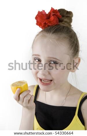 A little cute girl eating an lemon - stock photo