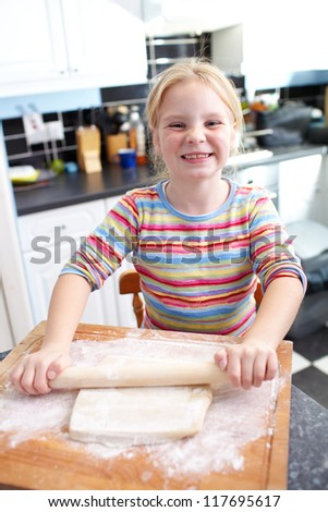 A little cute happy girl is cooking the dough for making biscuits in the kitchen - stock photo