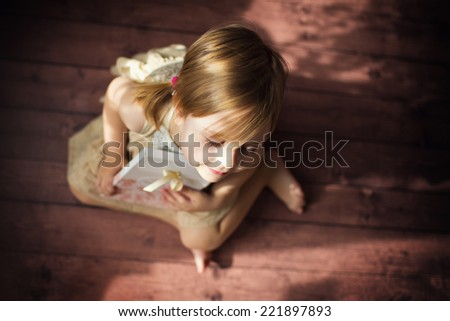 A little cute smiling girl sitting on the floor close up.  - stock photo