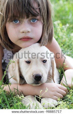 A little girl and her puppy, an English Cream Labrador-Golden Retriever mixed designer breed 7 week old puppy,  resting after playing together. Extreme shallow dof. - stock photo
