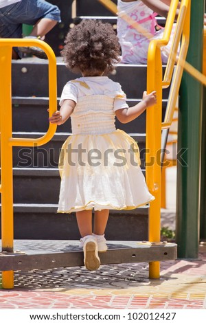 A little girl climbing up the stairs in a playground - stock photo