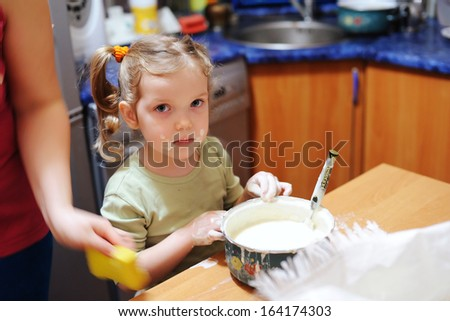 A little girl cooks  in the kitchen. - stock photo