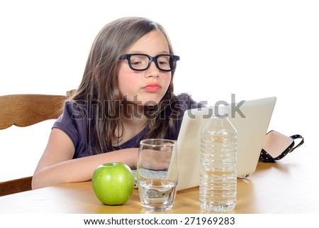 a little girl doing her homework on her computer on white - stock photo