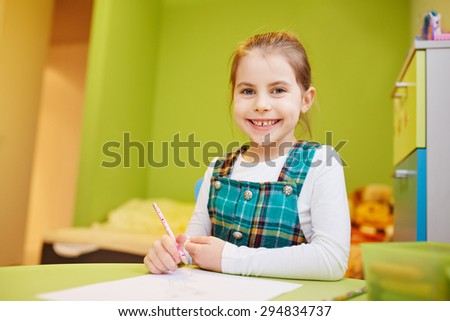 A little girl drawing  in her room - stock photo