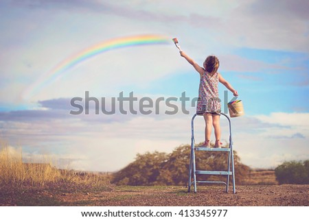 A little girl draws a rainbow standing on a ladder and holding a paint can - stock photo