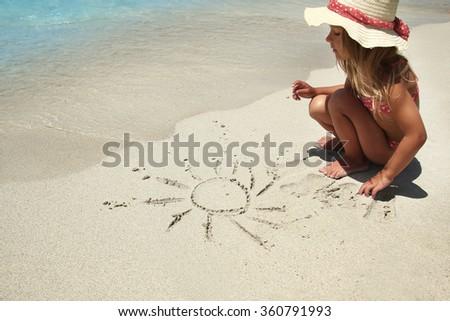 a little girl draws a sun in the sand on the beach - stock photo