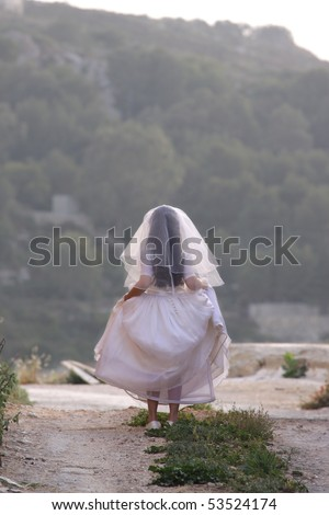 A little girl dressed up as a bride for her Holy Communion is walking away with her back against the camera - stock photo
