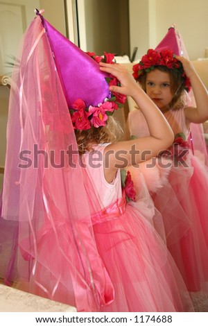 A little girl dressed up like a fairytale princess fixing her hat in a mirror. - stock photo