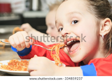 A Little girl eat pasta in the kitchen table - stock photo