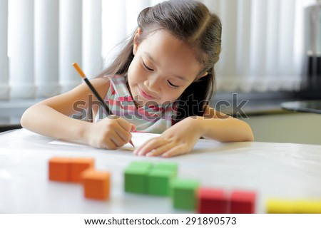 A little girl enjoying her learning at school - copy space available - stock photo