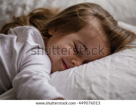 a little girl falls asleep in bed on white pillow, sleep - stock photo