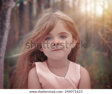A little girl has wind blowing in her hair and posing for a portrait in the nature woods for a photography or beauty concept. - stock photo