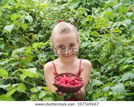 a little girl holding raspberries - stock photo