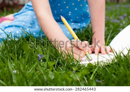 A little girl holds a pencil as she erases a mistake on a pad of drawing paper.  She is wearing a blue dress and is sitting in a grassy yard. - stock photo
