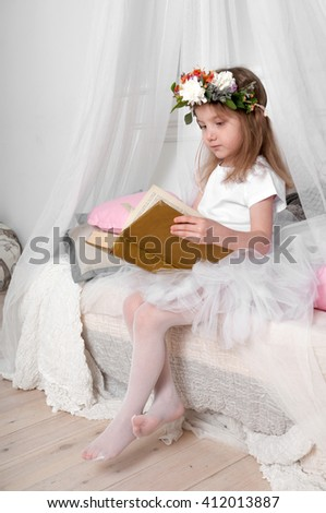 A little girl in a ballet dancer's fluffy skirt and having a wreath of fresh flowers on her head, sitting on a canopy bed and reading a book - stock photo