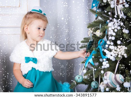 A little girl in a turquoise dress stands near a new-year tree and looks at her. A small child thinks a desire. - stock photo