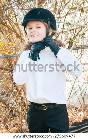A little girl in English riding attire is buckling her riding helmet.  She is wearing a black velvet helmet, leather riding gloves, white shirt, black jodhpurs and a gold bucked belt. - stock photo